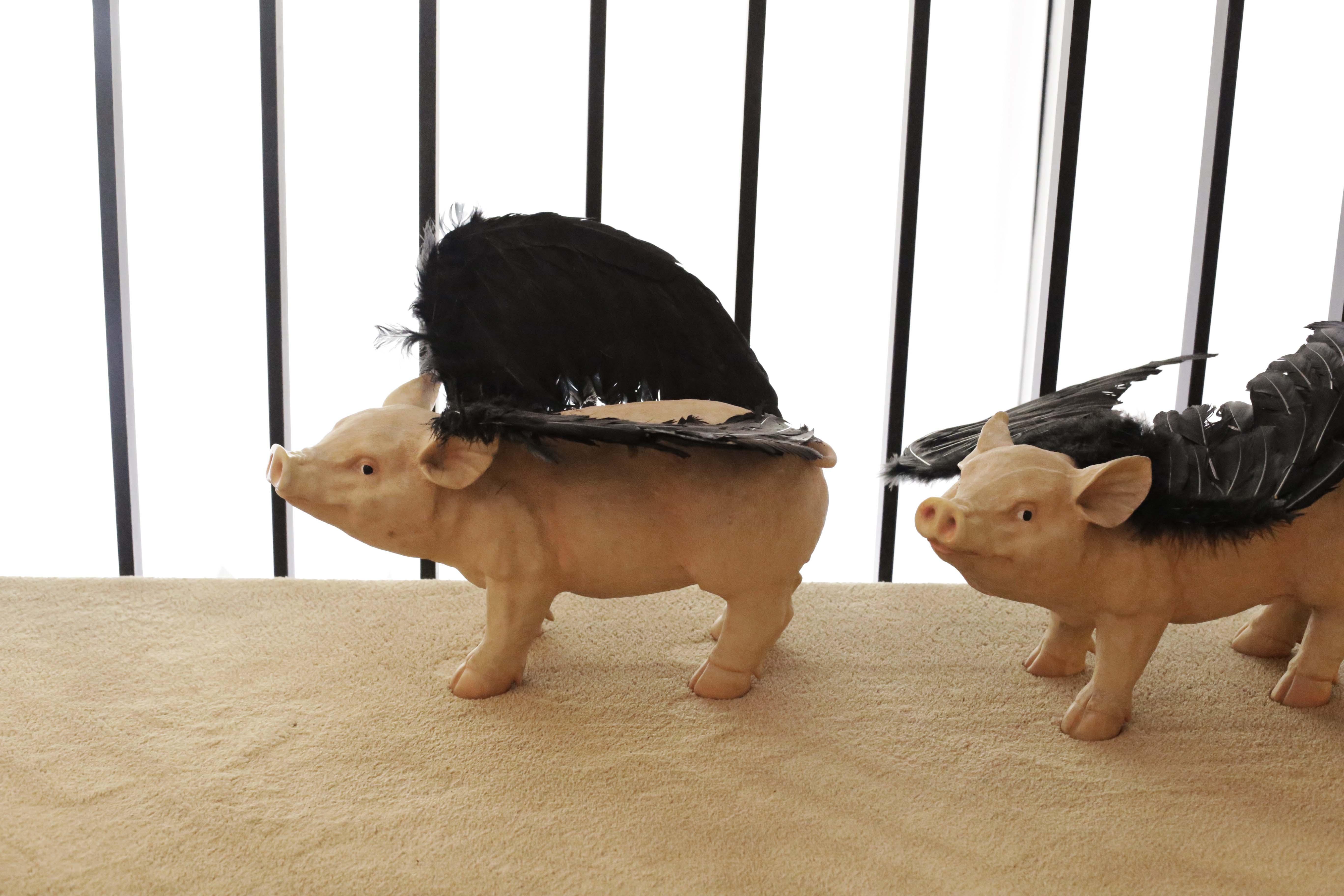 """Sus famosos iconoes de cerdos """"voladores"""" que encontramos en el suelo de la entrada al comedor"""