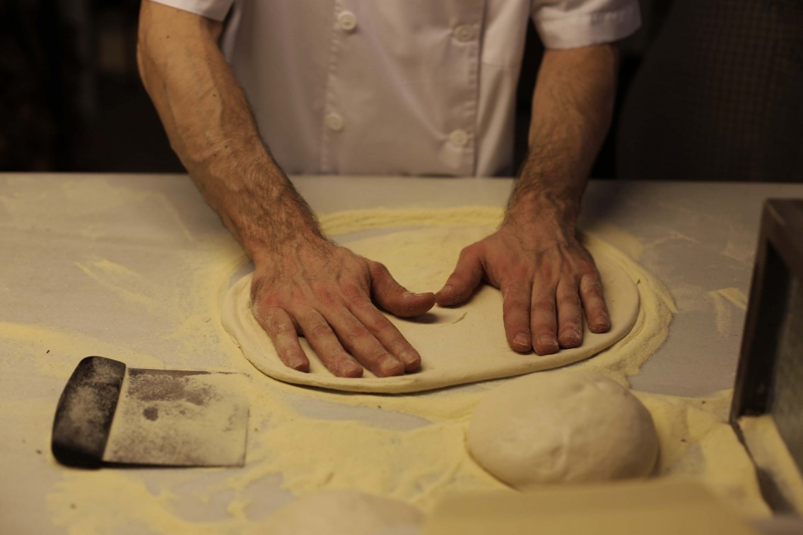 El maestro pizzero preparando la masa