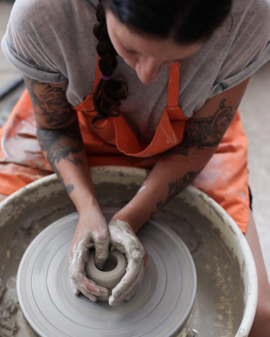 Otra compañera de clase agujereando la argila blanca para hacer un cilindro